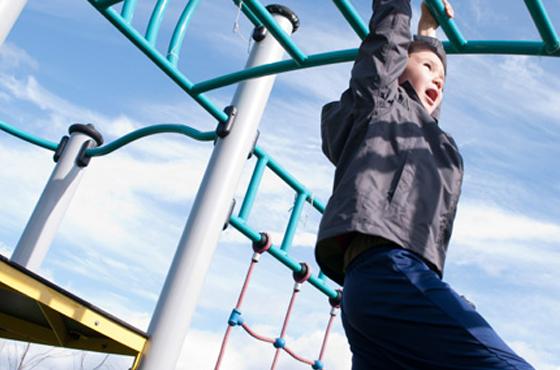 Boy swinging on a climbing frame